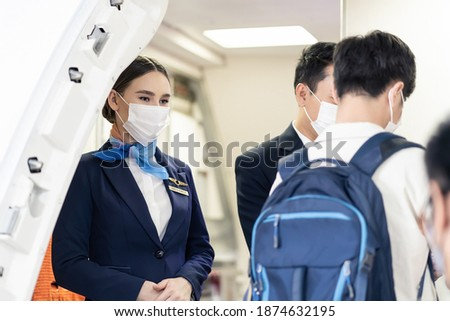 Asian flight attendants wearing face mask greeting passengers walking and coming on board in airplane during the Covid pandemic to prevent coronavirus infection. Healthcare in transportation concept. Royalty-Free Stock Photo #1874632195