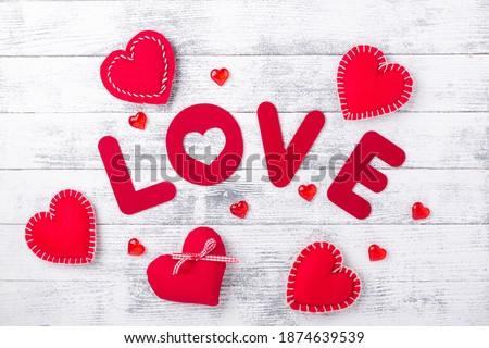 Word Love and red hearts on white wooden background Red textile letters. Valentines Day greeting card - Image