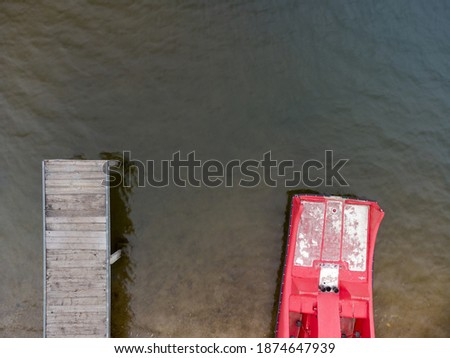 Aerial top down drone shot of wooden pier for swimmers and red paddleboat on the beach at lake of local recreation area #1874647939