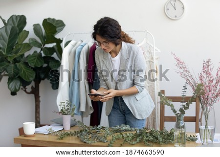 Arrangement step by step. Skilled millennial woman florist preparing tutorial master class of creating flower composition. Designer make photo of working process on mobile phone to post share online