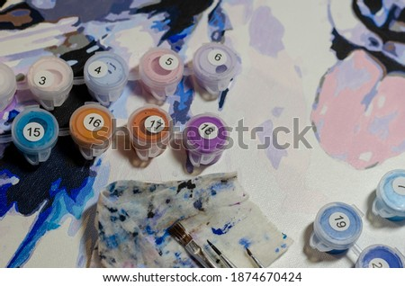 Colorful picture of husky dog on canvas, paint cans and brushes. Process of painting portrait of mischievous dog with his tongue out. Painting, art, creativity.