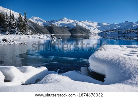 Winter lake with reflections of mountains in calm water. Garibaldi Lake in Whistler. British Columbia. Canada  Royalty-Free Stock Photo #1874678332