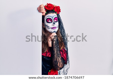 Young woman wearing day of the dead custome holding blank empty banner with hand on chin thinking about question, pensive expression. smiling and thoughtful face. doubt concept.