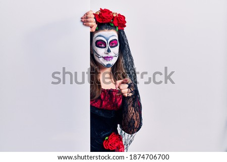Young woman wearing day of the dead custome holding blank empty banner pointing to you and the camera with fingers, smiling positive and cheerful