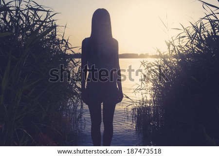Silhouette of a  female against water backlit shot toned image with copy space toned color. Silhouette of young girl looking into the distance, standing on the beach, at the sunset against the sun. #187473518