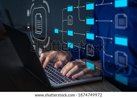 Document Management System (DMS) being setup by IT consultant working on laptop computer in office. Software for archiving, searching and managing corporate files and information. Business processes
