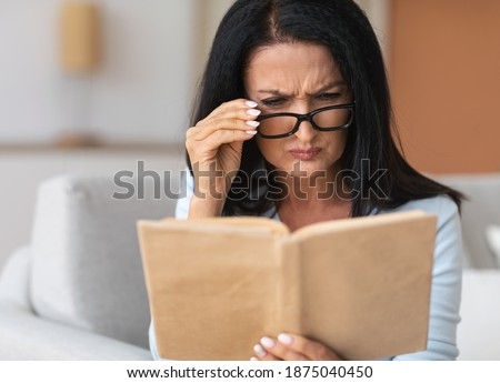 Portrait of confused senior woman squinting to see more clearly, wearing and touching eyeglasses, trying to read paper book, having difficulties seeing text because of bad vision problems and issues Royalty-Free Stock Photo #1875040450
