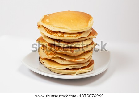 Stack of pancakes without any trimmings on a white plate in a white background.