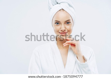 Studio shot of pretty beauty woman has washed hair, wears wrapped towel on head, has manicure, cute natural face, touches chin gently, looks with tender smile, dressed in bath robe, poses indoor Royalty-Free Stock Photo #1875094777