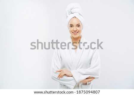 Beautiful smiling young woman has soft healthy skin after taking shower, wears bath robe and towel wrapped on head, enjoys spare time at home, isolated over white background. Wellness concept. Royalty-Free Stock Photo #1875094807