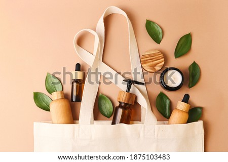 Open eco friendly cotton reusable bag with the different containers from the natural wood and brown glass.Fresh natural leafs around.Concept of organic,zero waste cosmetics.Woman bag with ac?essories. Royalty-Free Stock Photo #1875103483