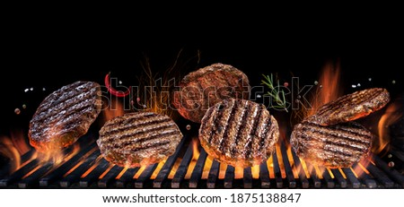 Grilled beef steaks in motion falling down on open grill. Conceptual photo of meat or barbeque cooking process.