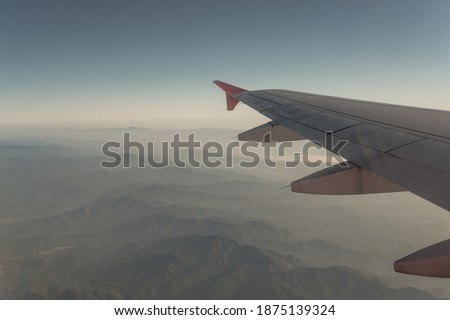 Sunrise with Wing of airplane. Mountain Landscape View from Airplane Window. #1875139324
