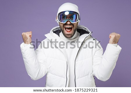 Joyful skier man in warm white windbreaker jacket ski goggles mask doing winner gesture spend extreme weekend winter season in mountains isolated on purple background. People lifestyle hobby concept Royalty-Free Stock Photo #1875229321
