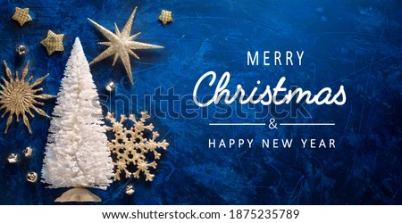 Art Merry Christmas and Happy Holidays greeting card, frame, banner. New Year. Noel. Christmas ornaments on blue background top view. Winter xmas holiday theme. Flat lay Royalty-Free Stock Photo #1875235789