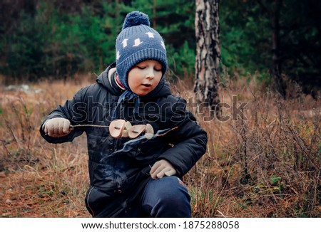 Boy in the woods near the fire.