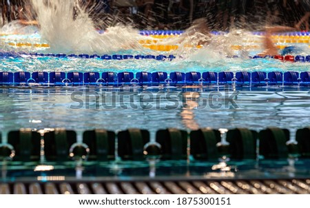 Close up photo of blue lane in swimming pool, blurry water splashes from fast freestyle swimmers