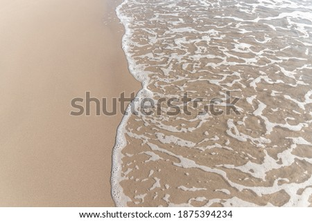 Sparkling waves hitting the shore on the beach, sand beige background image. Royalty-Free Stock Photo #1875394234