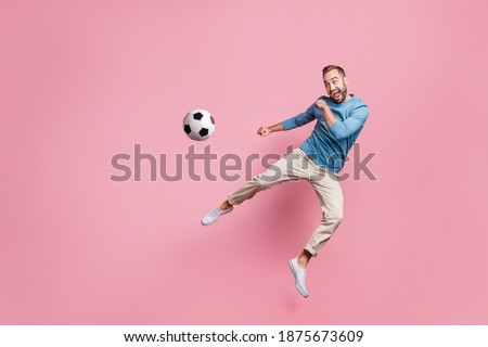 Full length photo of sweet strong young man dressed blue sweater jumping high kick foot ball isolated pink color background Royalty-Free Stock Photo #1875673609