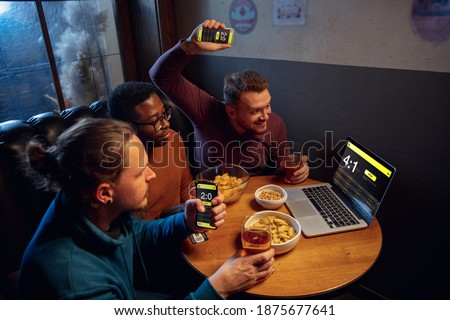Analyzing. Excited fans in bar with beer and mobile app for betting, score on their devices. Screen with match results, emotional friends cheering. Gambling, sport, finance, modern techn concept. Royalty-Free Stock Photo #1875677641
