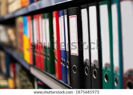 Paper binder shelf in a shop. Binder sale. Multicolor stationery folders Royalty-Free Stock Photo #1875681973