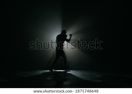 Fighter striking a blow. Professional sport. Fighting. Strength. Fighter in a moody light and grain mood.  boxer training with punching bag in dark sports hall Royalty-Free Stock Photo #1875748648