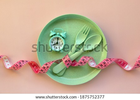 Creative flat lay composition with plate, alarm clock, spoon, fork and measuring tape on pink background. Intermittent fasting, ketogenic, diet concept.  Flat lay, copy space.  Royalty-Free Stock Photo #1875752377