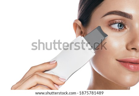Beautiful woman's face during ultrasonic peel skin procedure close-up. Cleansing facial skin, remove blackheads, isolated on white Royalty-Free Stock Photo #1875781489