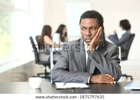 Lonely African-American businessman in office. Stop racism Royalty-Free Stock Photo #1875797635
