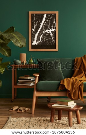 Stylish living room in house with modern retro interior design, velvet sofa, carpet on floor, brown wooden furniture, plants, poster mock up map, book, lamp and perosnal accessories in home decor. Royalty-Free Stock Photo #1875804136
