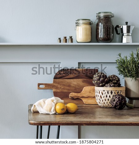 Stylish composition of kitchen interior with wooden family table, chairs, vegetables, herbs, plants, fruits, food supplies and kitchen accessories in gray concept of home decor.