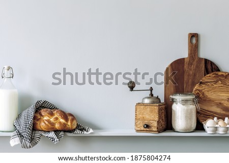 Modern composition on the kitchen interior with vegetables cutting board, food, herbs, kitchen accessories and copy space on the shelf.