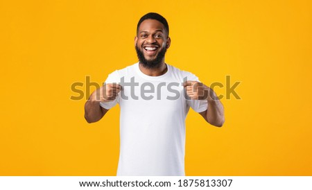 Cheerful Black Man Showing His White T-Shirt Smiling To Camera Standing Over Yellow Studio Background. Look There, Check This Out Concept. T-Shirt Mockup, Template For Your Text. Panorama Royalty-Free Stock Photo #1875813307