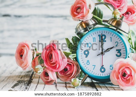 Set your clocks back with this clock and Ranunculus flowers over a white wooden table. Daylight saving time concept. Selective focus with blurred background.