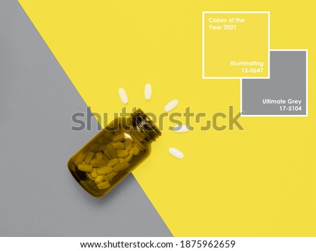 Medical pills in bottle on Illuminating Yellow and Ultimate Gray background with frame and text. Creative design demonstrating colors of the year 2021