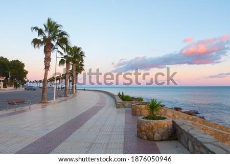 Beautiful promenade (boardwalk) near the mediterranean shore. Amazing sunset colors in the sky. Paseo Maritimo Alcossebre, Castellon province, Valencian Community, Spain. Royalty-Free Stock Photo #1876050946