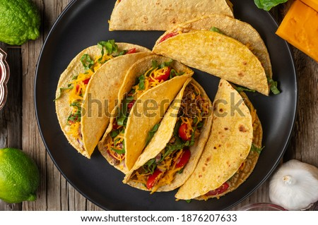 View from above of plate with mexican tacos on rustic wooden table background. Concept of traditional meal. Appetizing photo for menu or cookbook. #1876207633