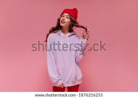 Pretty curly girl in red hat and purple oversized hoodie smiles on pink background. Charming woman coquettishly plays hair on isolated. Royalty-Free Stock Photo #1876216255
