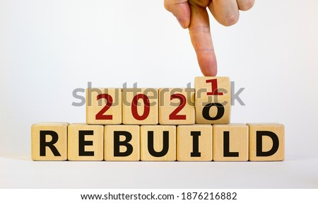 Symbol of 2021 rebuild. Male hand flips wooden cubes and changes the inscription 'Rebuild 2020' to 'Rebuild 2021'. Beautiful white background, copy space. Business and 2021 rebuild concept. Royalty-Free Stock Photo #1876216882