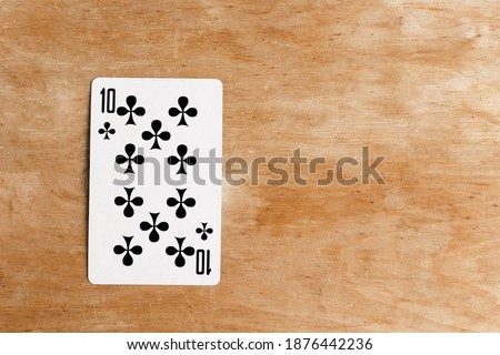 Ten of Clubs on wooden background, top view, copy space