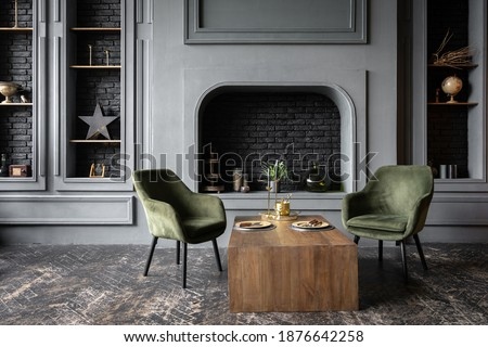 Elegant living room with loft interior design, comfort armchairs near wooden table against decorative fireplace and home decor in fancy apartment Royalty-Free Stock Photo #1876642258
