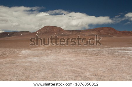 Adventure and explore. Traveling along the dirt road across the arid desert and mountains. View of the extreme route very high in the Andes cordillera.  Royalty-Free Stock Photo #1876850812