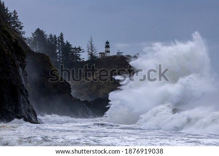 Large waves crashing against cliffs at Cape Disappointment on the Washington coast during King Tide Royalty-Free Stock Photo #1876919038