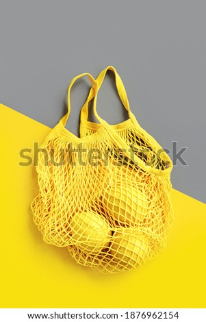 Yellow Cotton net bag with lemons on Grey background. Colors of the year 2021 Ultimate Grey and Illuminating. Color trend palette. Stylish background