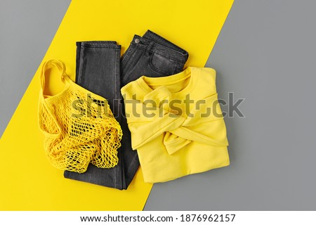 Yellow  sweater, jeans and net bag on Grey background. Colors of the year 2021 Ultimate Grey and Illuminating. Women's stylish autumn or winter clothes set. Flat lay, top view.