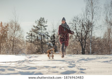 Girl in a red down jacket on walk with purebred beagle puppy in winter park. Woman and dog in forest. Girl runs and plays in the snow with pet. Winter sunny landscape. Stylish toning and soft focus. Royalty-Free Stock Photo #1876963483