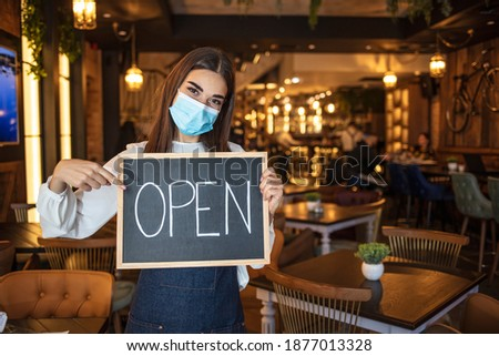 Caucasian female waitress reopening her cafe. Portrait of a young Caucasian female waitress wearing an apron and a face mask, standing at the entrance of a store and holding a sign that says Open Royalty-Free Stock Photo #1877013328