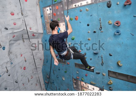 Young caucasian man wearing protective face mask rappelling at indoor artificial rock climbing wall. New normal concept. #1877022283