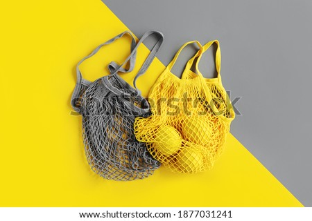 Reusable shopping bags with lemons. Colors of the year 2021 Ultimate Grey and Illuminating. Color trend palette. Stylish background