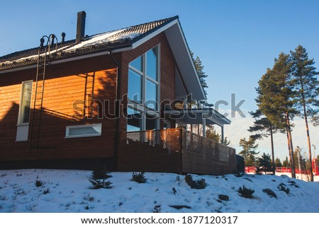 A view of cozy wooden scandinavian cabin cottage chalet house covered in snow near ski resort in winter with the lights on, evening picture